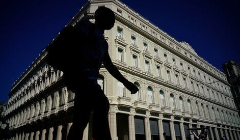 A man walks in front of the Manzana de Gomez Kempinski five-star hotel in Havana, Cuba. Five months into the Trump administration, Cuba has a new set of American defenders _ a coalition of high-tech firms, farming interests, travel companies and young Cuban-Americans thrown into action by the looming announcement of a new Cuba policy