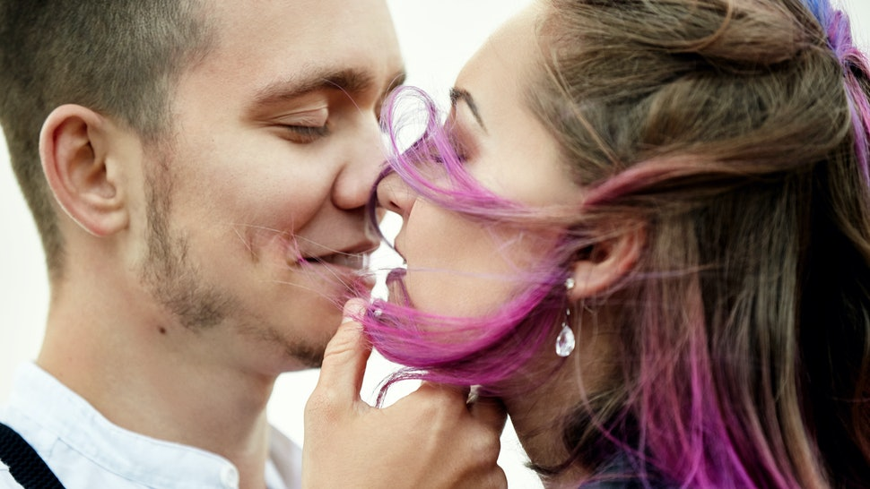 Embrace and kiss a couple in love on a spring morning in nature. Valentine's day, a close relationship between a man and a woman. Man kissing girl with bright colored hair, creative coloring