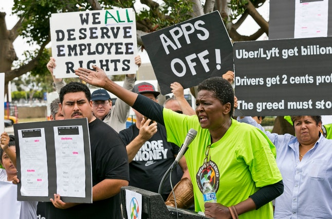 Uber driver Estaphanie St. Just joins drivers for ride-hailing giants Uber and Lyft, as they hold a rally at a park near Los Angeles International Airport, Wednesday, May, 8, 2019, in Los Angeles. Some drivers for ride-hailing giants Uber and Lyft turned off their apps to protest what they say are declining wages as both companies rake in billions of dollars from investors