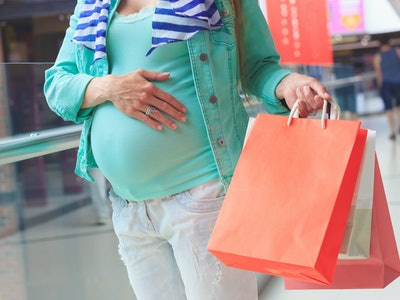 pregnant woman with paper packages in the mall, shopping on black friday