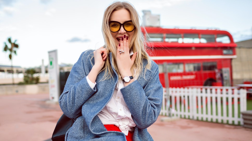 Close up city outdoor autumn spring mid season image of happy magnificent blonde exited woman smiling and laughing, traveling mood, stylish smart casual outfit, coat, backpack and glasses.