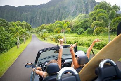 Road trip travel - girls driving car in freedom. Happy young girls cheering in convertible car on su...