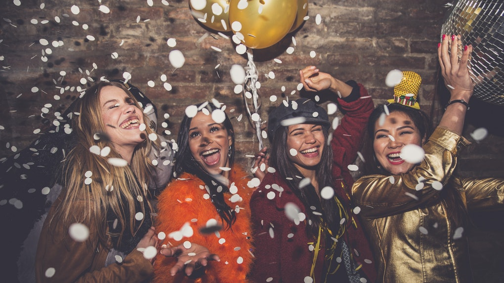 A group of girl friends dances, laughs, and parties while confetti falls on New Year's Eve.