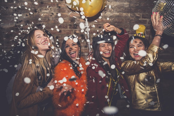 A group of friends laugh and dance under confetti on New Year's Eve.