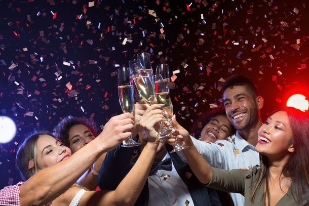 A group of friends laughs and toasts their champagne glasses while confetti falls on New Year's Eve.