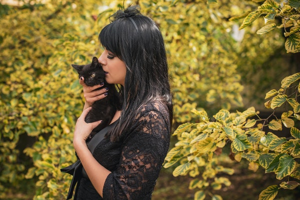Halloween party concept, mysterious girl with black cat. Beautiful young dark witch woman. Inspiration for halloween celebration, ideas and simple nice detail