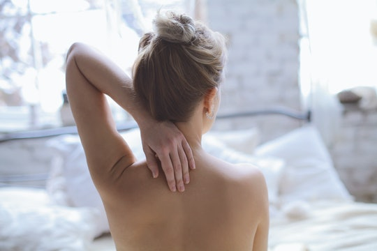 a woman on a bed with her back to the camera and her arm raised