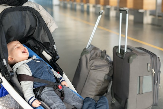 Screaming baby boy sitting in stroller near luggage at airport terminal. Child in carriage near chec...