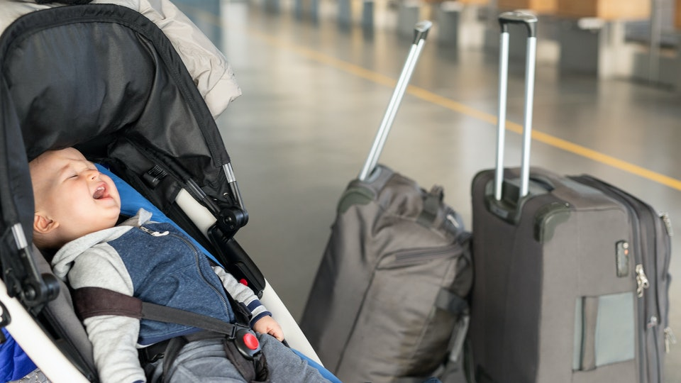 Screaming baby boy sitting in stroller near luggage at airport terminal. Child in carriage near check-in desk counter.