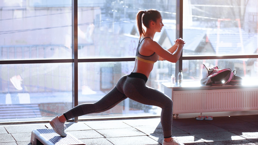 A woman in workout leggings and a sports bra does a lunge in front of a window.