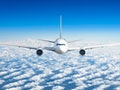 Passenger airplane flying at flight level high in the sky above the clouds and blue sky. View direct...