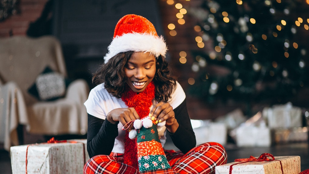 African american woman holding christmas presents by the christmas tree