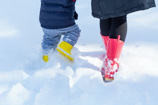 Experts say wearing your own boots can convince your toddler to keep theirs on.