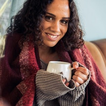 Young hygge woman drinking warm coffee on sofa at home