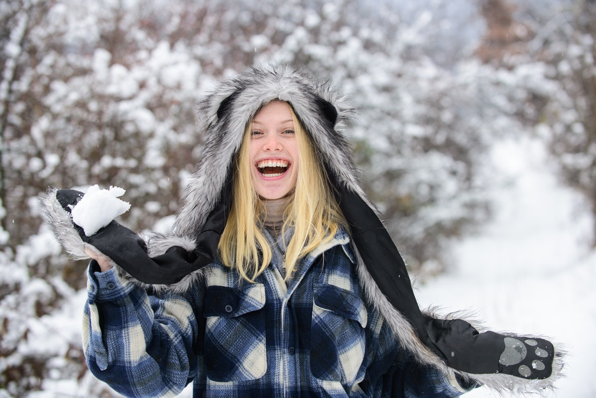 Girl playing with snow. Girl in mittens hold snowball. Happy woman holds snowball in hands. Winterti...