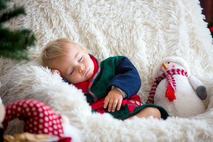Baby boy, cute child, wearing santa claus robe sitting in rocking chair with Christmas tree and ligh...