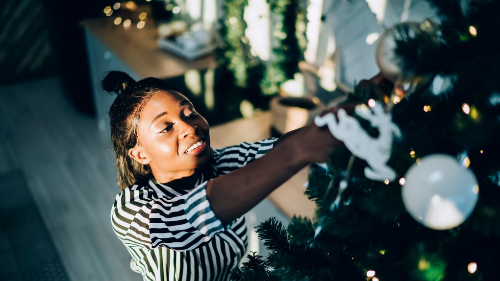 A happy woman in a black and white striped shirt decorates her Christmas tree while listening to music.