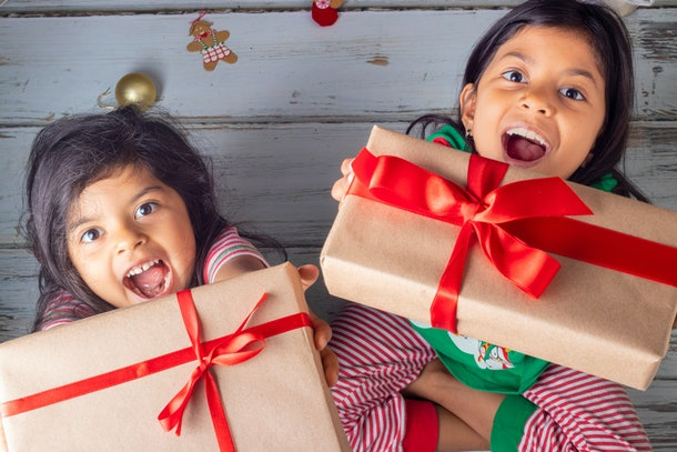 Little sisters opening their gifts on Christmas day