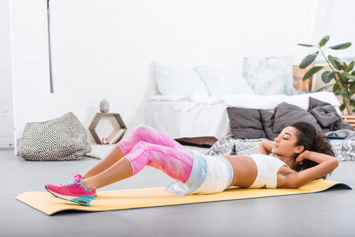 A woman in workout clothes does sit-ups in her home on a yoga mat.