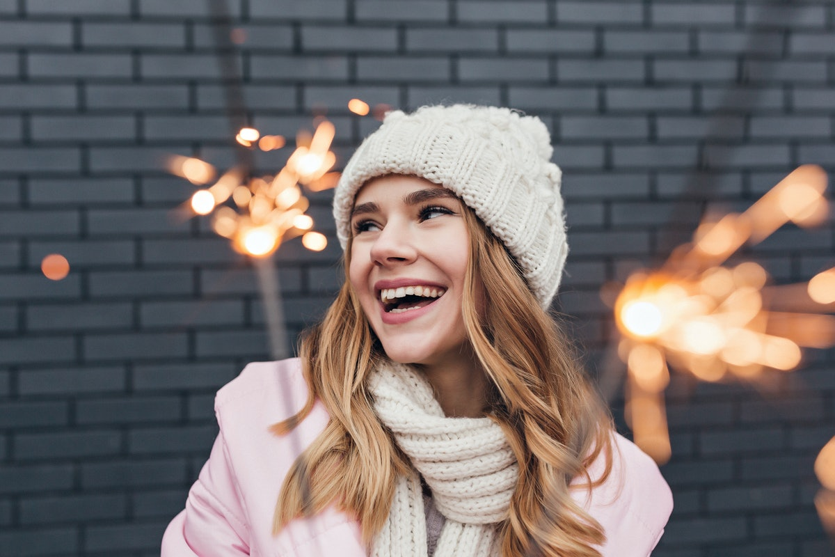 Happy cute girl in winter hat posing with sparkler. Outdoor shot of interested blonde woman having fun in holidays.