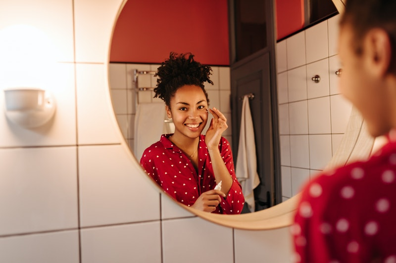 Brown-eyed woman in great mood looks in bathroom mirror and applies cream