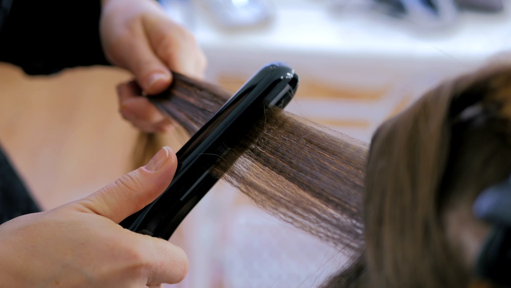 Professional hairdresser, stylist doing hairstyle and using straightener on beautiful long hair of client in white make up room. Beauty and haircare concept