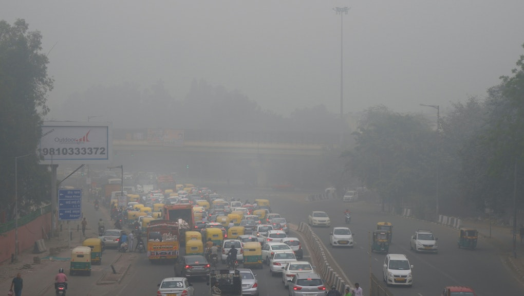"Vehicles wait for a signal at a crossing as the city enveloped in smog in New Delhi, India. Authorities in New Delhi are restricting the use of private vehicles on the roads under an ""odd-even"" scheme based on license plates to control vehicular pollution as the national capital continues to gasp under toxic smog"