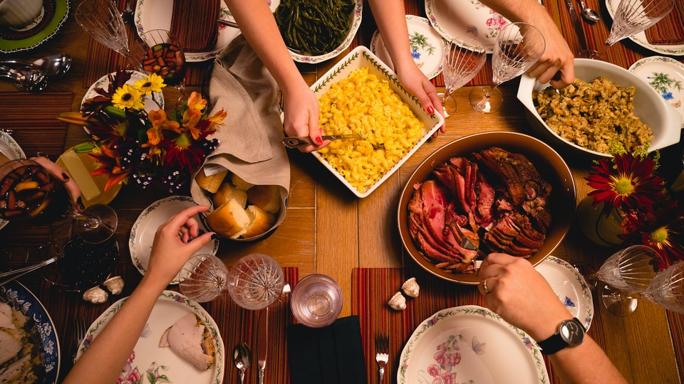 A group of guests sit down for Thanksgiving dinner.