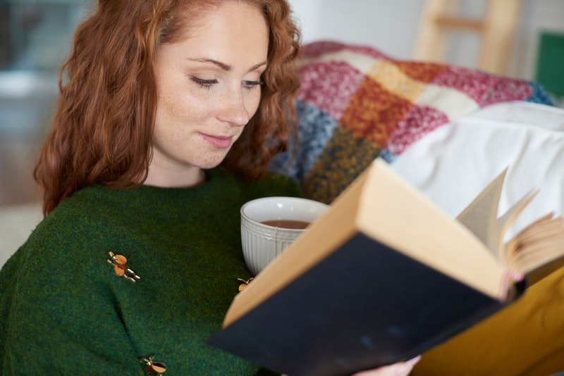 Smiling woman reading book in winter day
