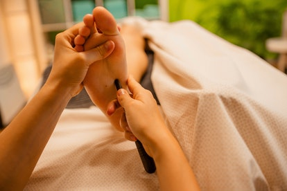 Woman having a relaxing thai massage with foot massage stick in the spa beauty salon. Body care