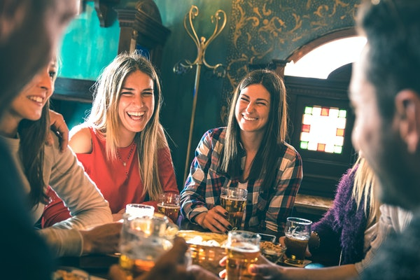 A group of happy friends, with two women smiling in the center, drink beer at a beer hall.