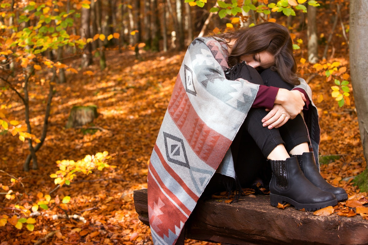 young brunette woman sitting outside in autumn and is sad