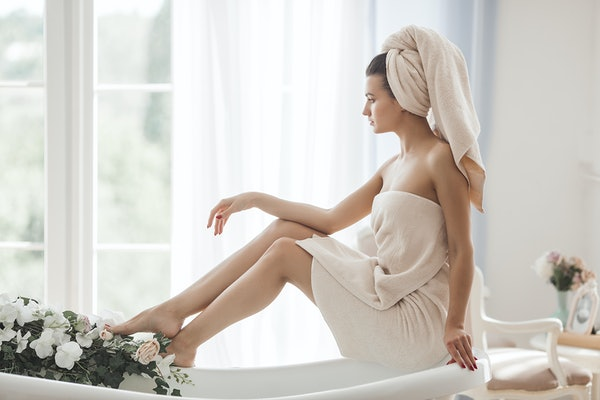 A woman sits by a bathtub with flowers, in a cream-colored bath towel and towel around her hair looking out the window.