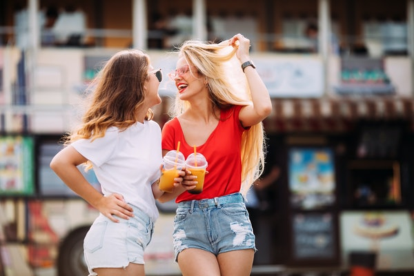 Two stylish girls laugh while they hold drinks in their hands and walk through an amusement park.