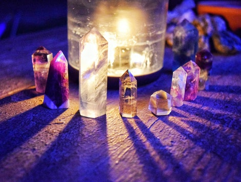 Crystal towers around a candle casting shadows under a full moon.