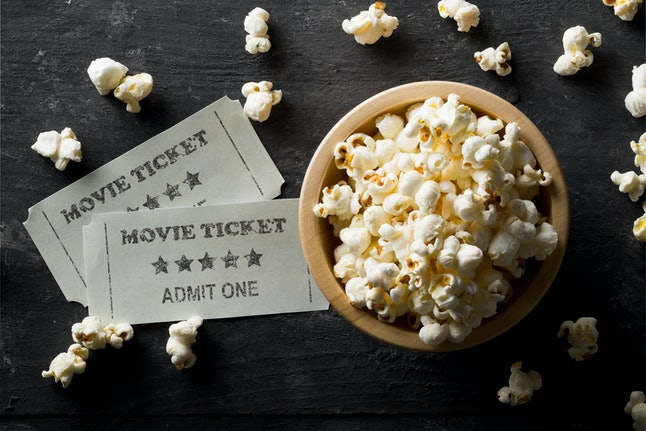 Movie tickets and bowl of popcorn on dark background. Home theatre movie or series night concept. Flat lay top view from above.