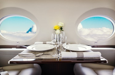 Luxury interior in bright colors of genuine leather in the business jet, sky and clouds through the ...