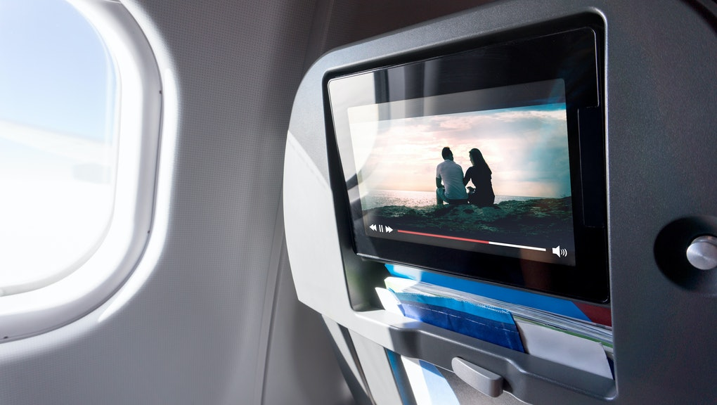 Watching movie on an airplane touch screen. Imaginary film playing on a video player in monitor during long flight. Entertainment service system in aircraft.