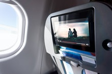 Watching movie on an airplane touch screen. Imaginary film playing on a video player in monitor duri...