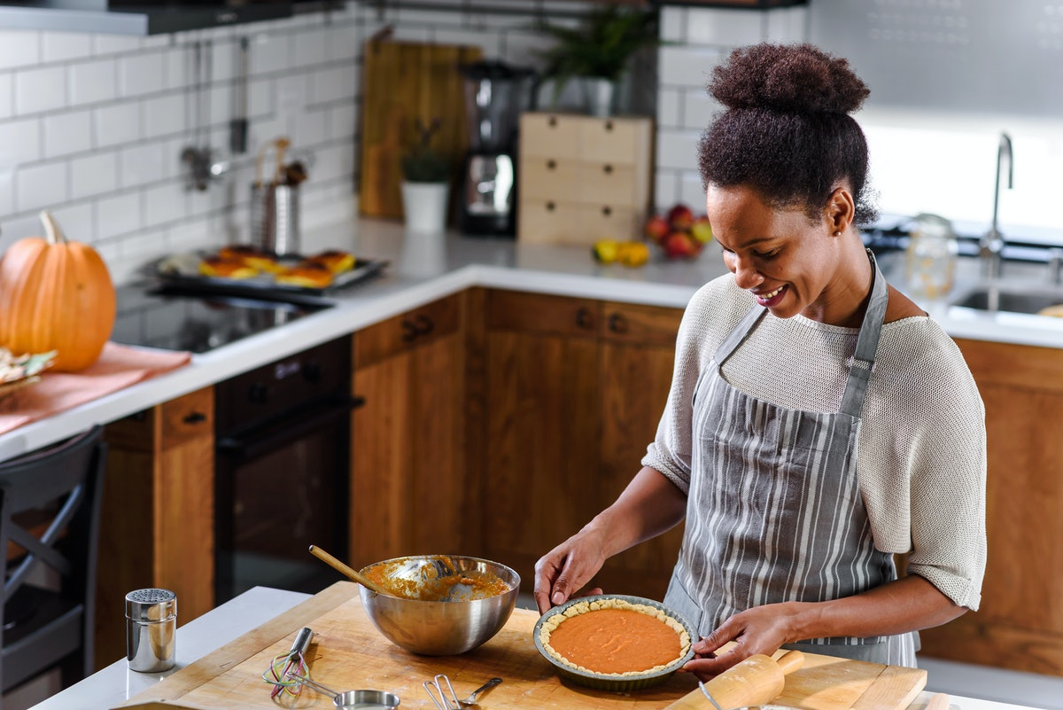 A smiling woman with an apron on smiles and looks down at her sweet potato pie for the holidays in h...