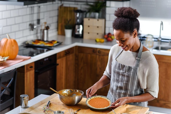A smiling woman with an apron on smiles and looks down at her sweet potato pie for the holidays in her kitchen.