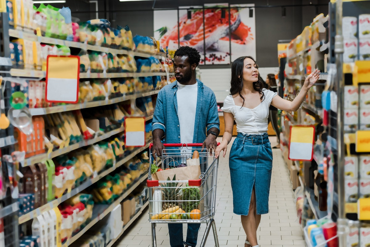 handsome man walking with shopping cart near attractive asian girl gesturing in store