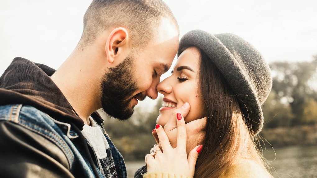 Lovely couple. Girl in hat close eyes. Boyfriend hugging her face. Romantic day. Outdoor. Cozy love. Happy love