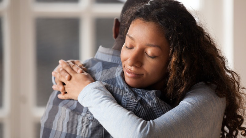 Happy mixed race woman hug black man husband glad to make peace after fight, loving young girlfriend reconcile with beloved boyfriend, embracing holding in arms. Healthy relationships concept