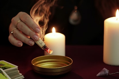 Witch is fortune teller in black mantle holding burning paper with spell over bowl. Tarot cards, amethyst stone, white candles on dark mystic background. Occult, esoteric, divination and wicca concept