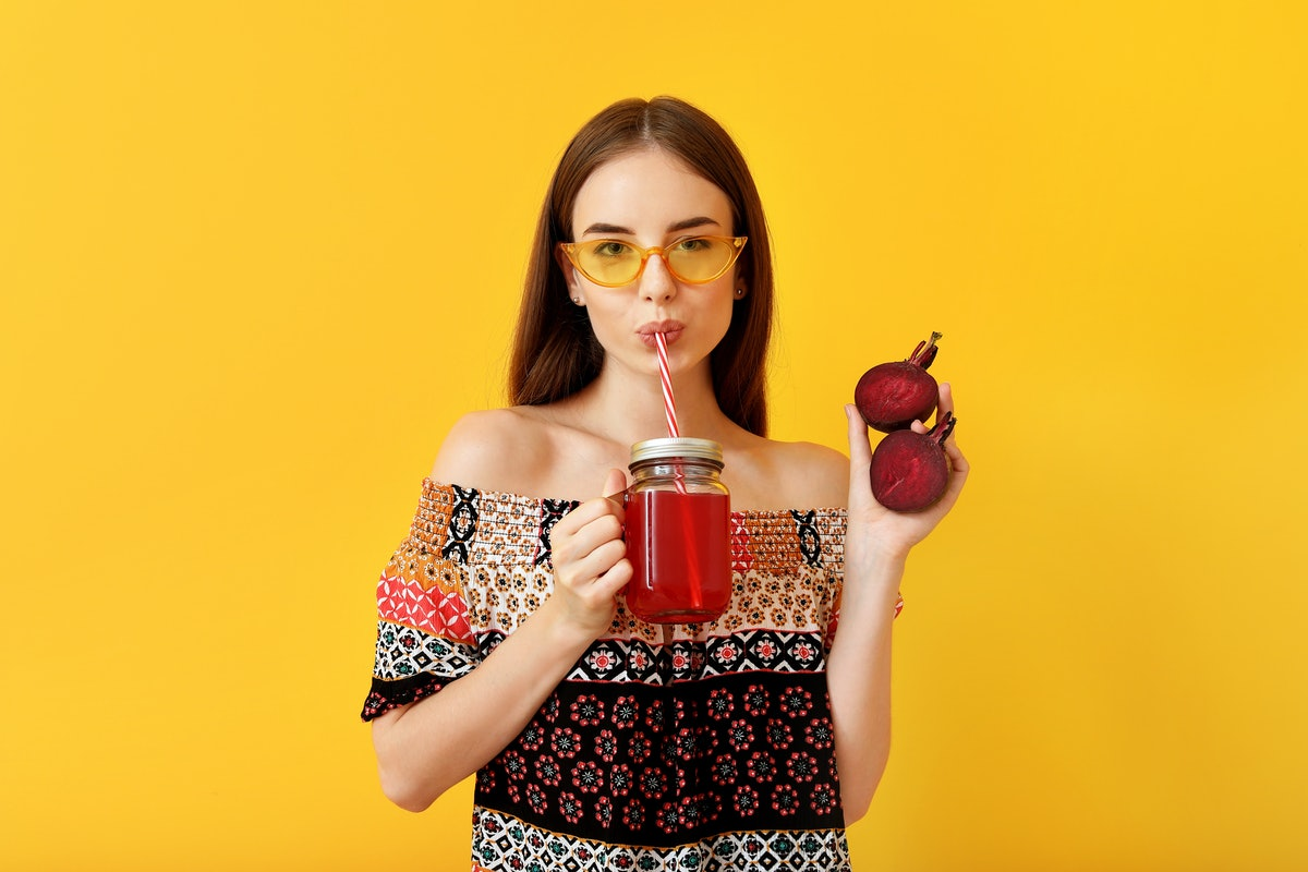Young woman drinking healthy beet juice on color background