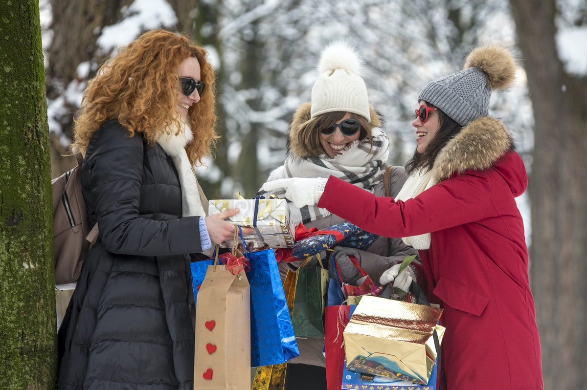 Group of smiling friends celebrate and joke after making winter shopping during Christmas festivitie...