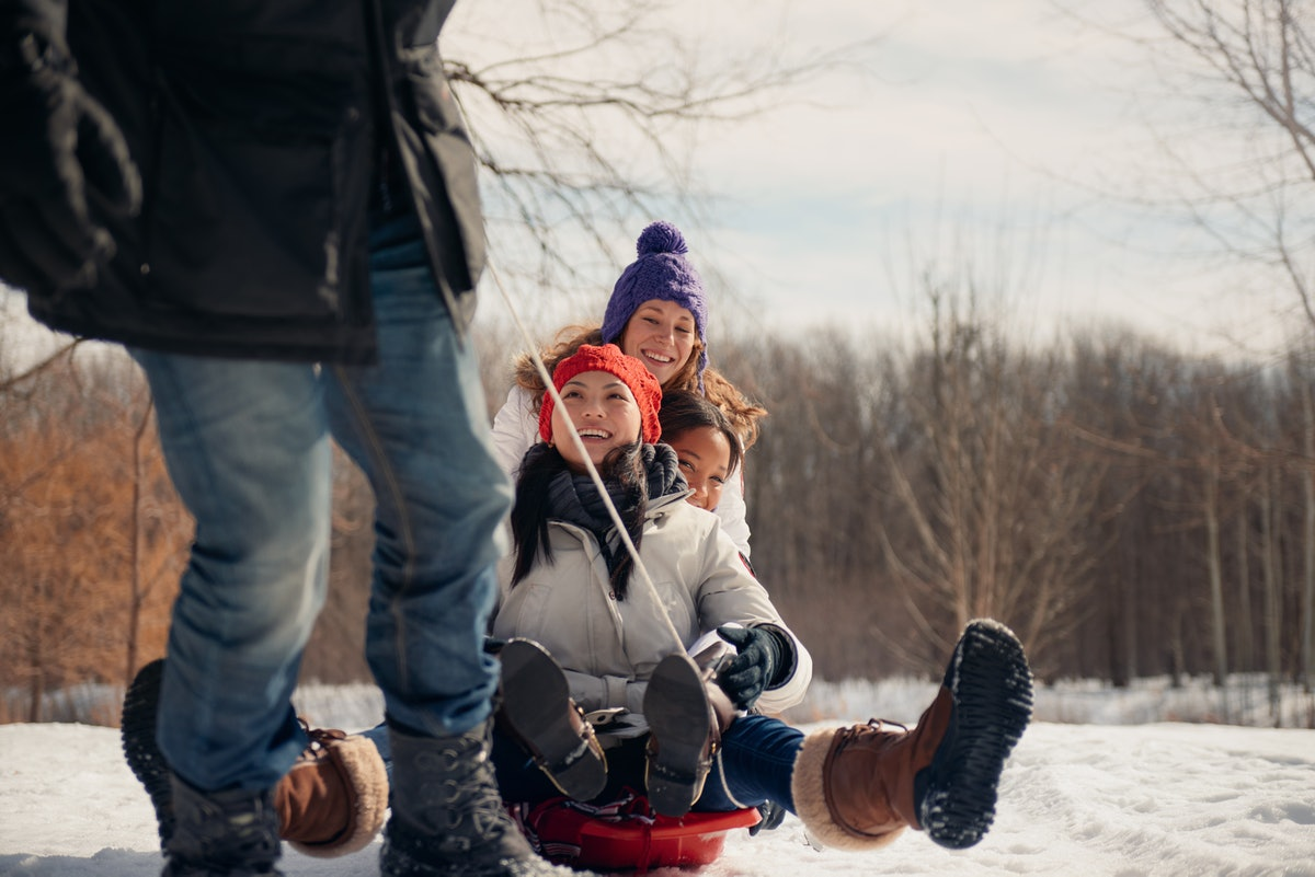 Group of friends enjoying pulling a sled in the snow in winter