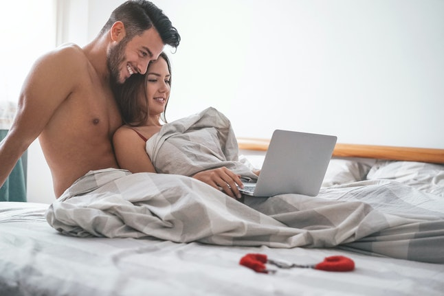 Happy couple watching on computer while lying on bed under blanket - Young lover watching role games sex video on laptop - People, sexual, intimate, youth and technology concept