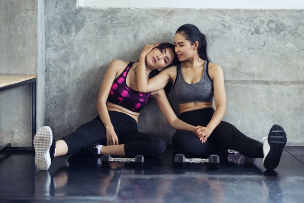 two tired Asian slim body female friends or lesbian couple sit and rest in fitness gym after dumbbell exercise, bodybuilder, healthy lifestyle,  workout, sport training concept.